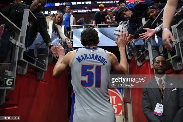 Boban Marjanovic of the Detroit Pistons high fives fans after the game against the Oklahoma City Thunder on January 27 2018 at Little Caesars Arena...