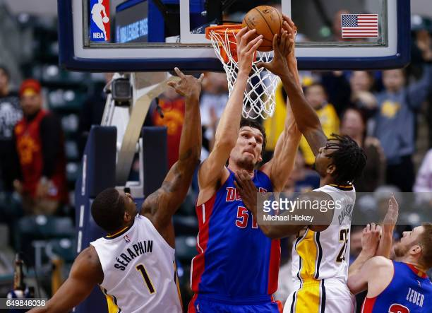 Boban Marjanovic of the Detroit Pistons reaches for the rebound against Kevin Seraphin and Rakeem Christmas of the Indiana Pacers at Bankers Life...