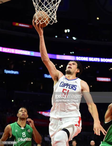 Boban Marjanovic of the Los Angeles Clippers drives to the basket for a layup past Scott Machado of Maccabi Haifa in the first half of the game at...