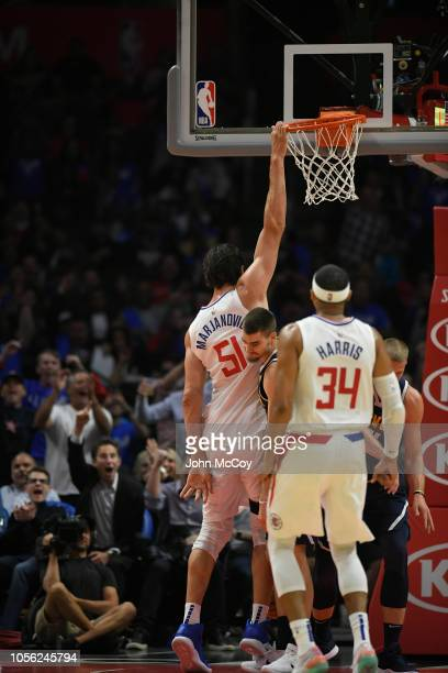 Boban Marjanovic of the Los Angeles Clippers holds onto the rim while standing on his toes after a dunk against the Denver Nuggets during the season...