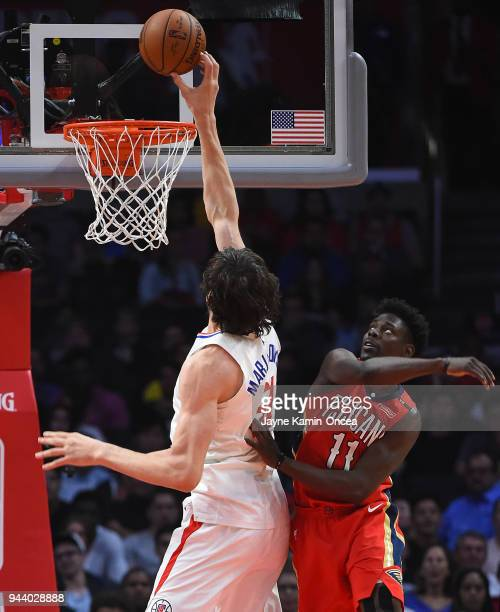 Boban Marjanovic of the Los Angeles Clippers is fouled by Jrue Holiday of the New Orleans Pelicans as he goes for a dunk in the second half of the...