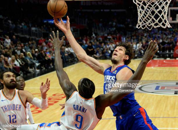 Boban Marjanovic of the Los Angeles Clippers shoots a basket as he is fouled by Jerami Grant of the Oklahoma City Thunder during the second half of a...