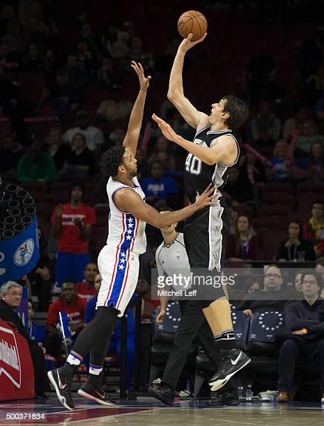Boban Marjanovic of the San Antonio Spurs attempts a shot over Jahlil Okafor of the Philadelphia 76ers on December 7 2015 at the Wells Fargo Center...
