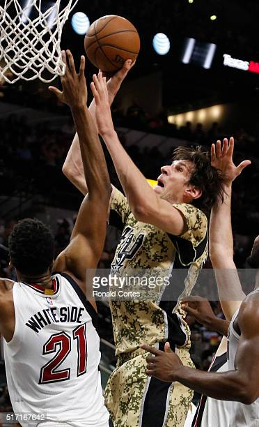 Boban Marjanovic of the San Antonio Spurs scores two against Hassan Whiteside of the Miami Heat at ATT Center on March 19 2016 in San Antonio Texas...