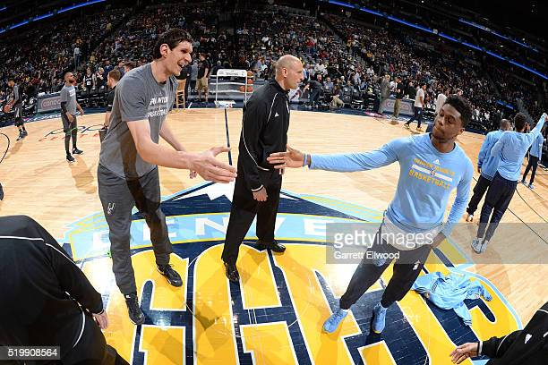 Boban Marjanovic of the San Antonio Spurs shakes hands with Emmanuel Mudiay of the Denver Nuggets before the game on April 8 2016 at the Pepsi Center...