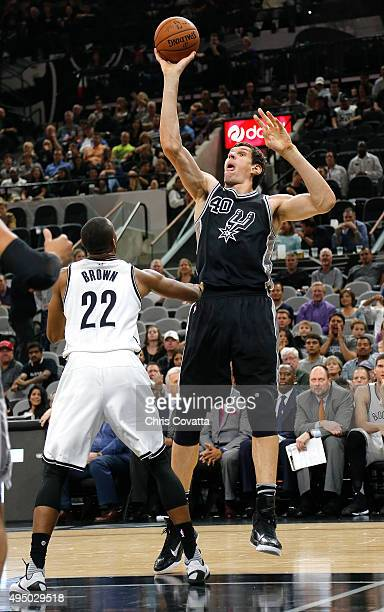 Boban Marjanovic of the San Antonio Spurs shoots over Markel Brown of the Brooklyn Nets at the ATT Center on October 30 2015 in San Antonio Texas...