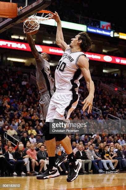 Boban Marjanovic of the San Antonio Spurs slam dunks the ball past Archie Goodwin of the Phoenix Suns during the second half of the NBA game at...