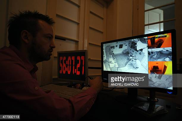 """Boban Melkus monitors players taking part in the virtual """"Escape Room"""" game in Novi Sad, on January 31, 2014. Those fed up with computer gaming..."""