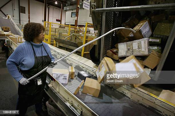 Bobbi Crump loads mail onto a conveyor at the United States Postal Service Chicago Logistics and Distribution Center on December 17 2012 in Elk Grove...