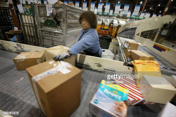 Bobbi Crump moves mail on a conveyor at the United States Postal Service Chicago Logistics and Distribution Center on December 17 2012 in Elk Grove...