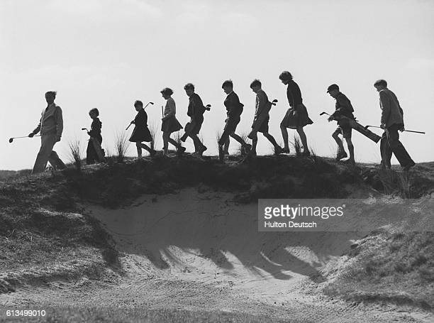 Bobbie Halsall leads young pupils over the Royal Birkdale course at Southport England | Location Royal Birkdale Southport England UK