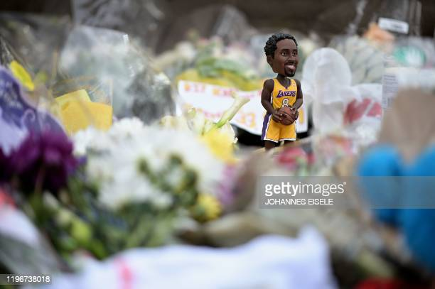 A bobblehead sports doll of Kobe Bryant is seen between memorial flowers outside Bryant Gymnasium at Lower Merion High School where basketball legend...