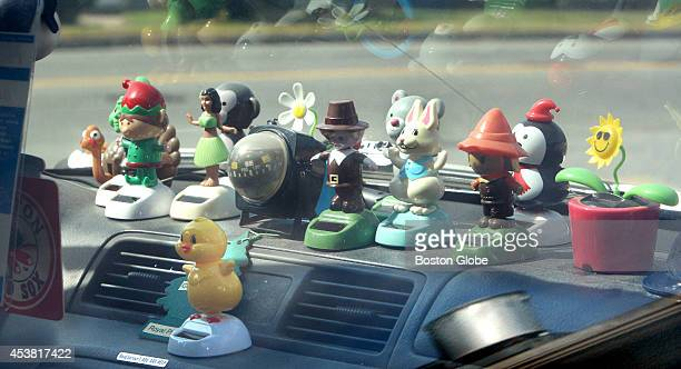Bobbleheads line dashboard of car parked in Peabody Mass August 16 2014