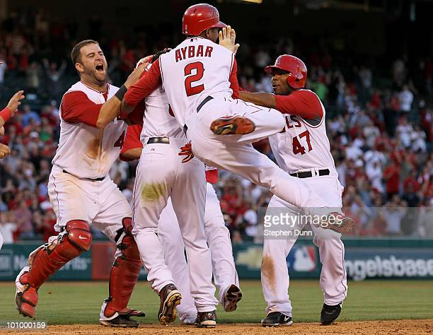 Bobby Abreu of the Los Angeles Angels of Anaheim is mobbed by Mike Napoli Erick Aybar and Howie Kendrick after Abreu's walk off RBI single with two...