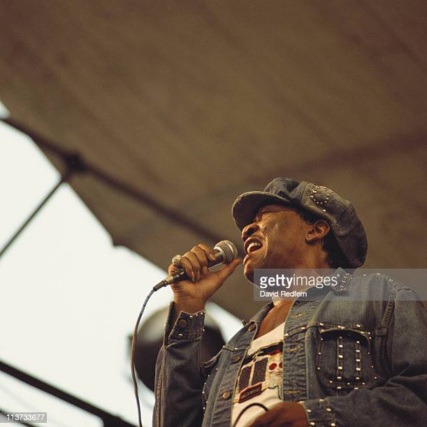 Bobby Bland, U.S. Blues and soul singer, wearing a studded denim jacket and matching denim cap while singing into a microphone during a live concert...