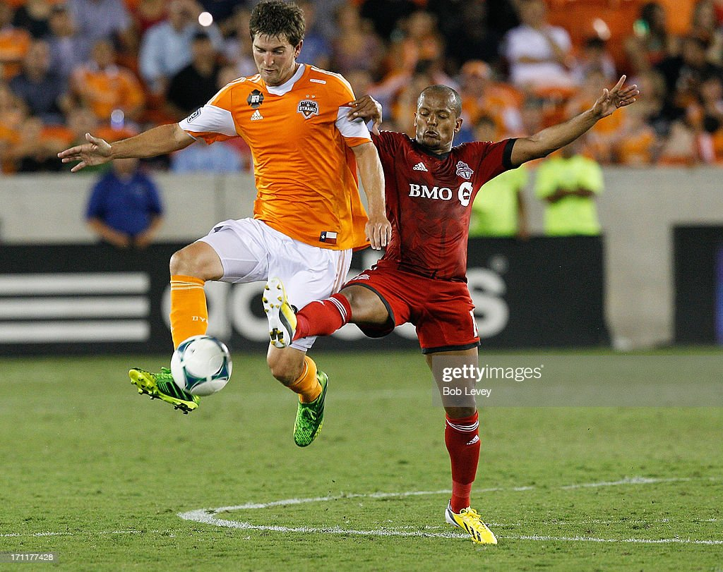 Bobby Boswell #32 of Houston Dynamo keeps the ball away from Robert Earnshaw #10 of Toronto FC at BBVA Compass Stadium on June 22, 2013 in Houston, Texas.