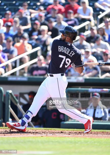 Bobby Bradley of the Cleveland Indians follows through on a swing during a spring training game against the Texas Rangers looks on at Goodyear...