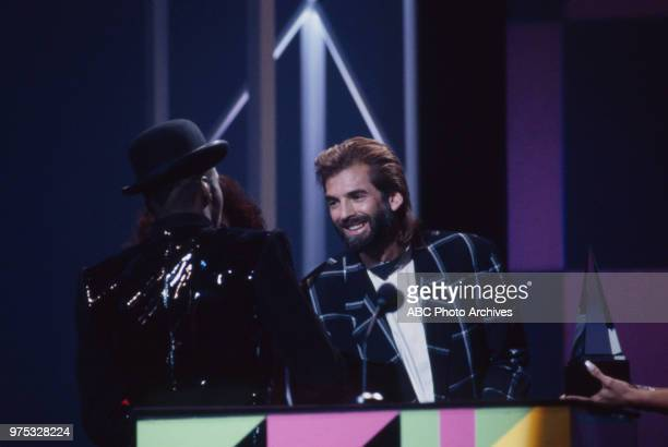 Bobby Brown Kenny Loggins Bobby Brown receiving award on the 17th Annual American Music Awards Shrine Auditorium January 22 1990