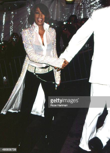 Bobby Brown leads singer Whitney Houston by the hand at the Costume Institute gala at the Metropolitan Museum, New York, New York, 1999.