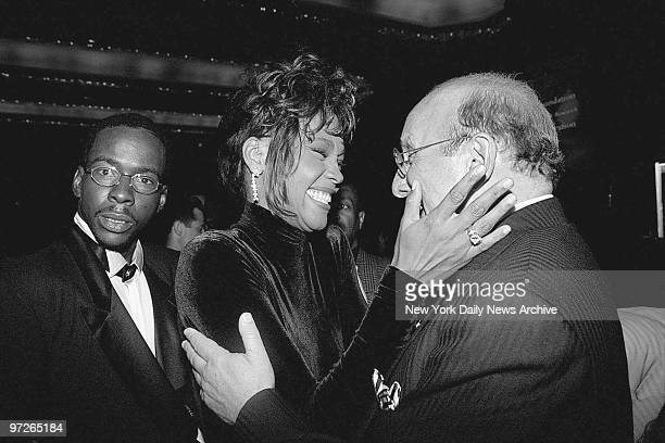 Bobby Brown looks on as his wife Whitney Houston congratulates Clive Davis president of Arista Records at a TJ Martell benefit dinner for held for...
