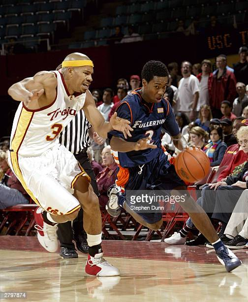 Bobby Brown of the Cal State Fullerton Titans tries to drive past Desmon Farmer of the USC Trojans on December 9 2003 at the Los Angeles Sports Arena...