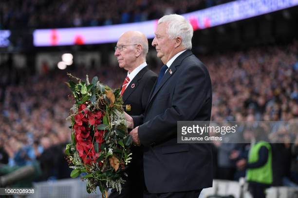 Bobby Charlton and Mike Summerbee bring out a wreath for Remembrance Day prior to the Premier League match between Manchester City and Manchester...