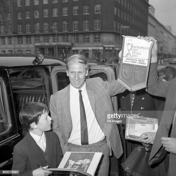 Bobby Charlton captain of European Cup winners Manchester United with fans and a souvenir pennant outside the Bloomsbury hotel in London where the...
