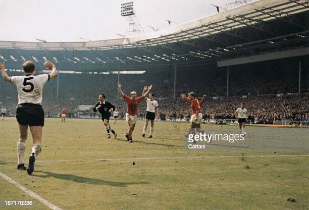Bobby Charlton holds his hands up as West German players protest after Geoff Hurst scores the controversial third goal during the World Cup final at...