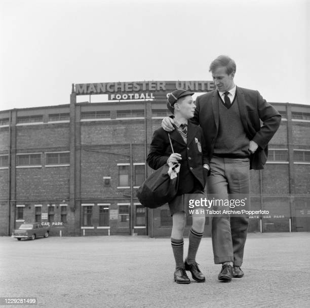 Bobby Charlton of Manchester United and a young boy named Charles Adamson leave the ground after a training session at Old Trafford in Manchester,...