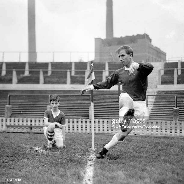 Bobby Charlton of Manchester United taking a corner kick, closely watched by a young boy named Charles Adamson during a training session at Old...