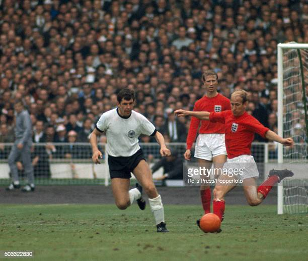 Bobby Charlton on the ball for England watched by his brother Jack Charlton and Lothar Emmerich of West Germany during the FIFA World Cup Final...