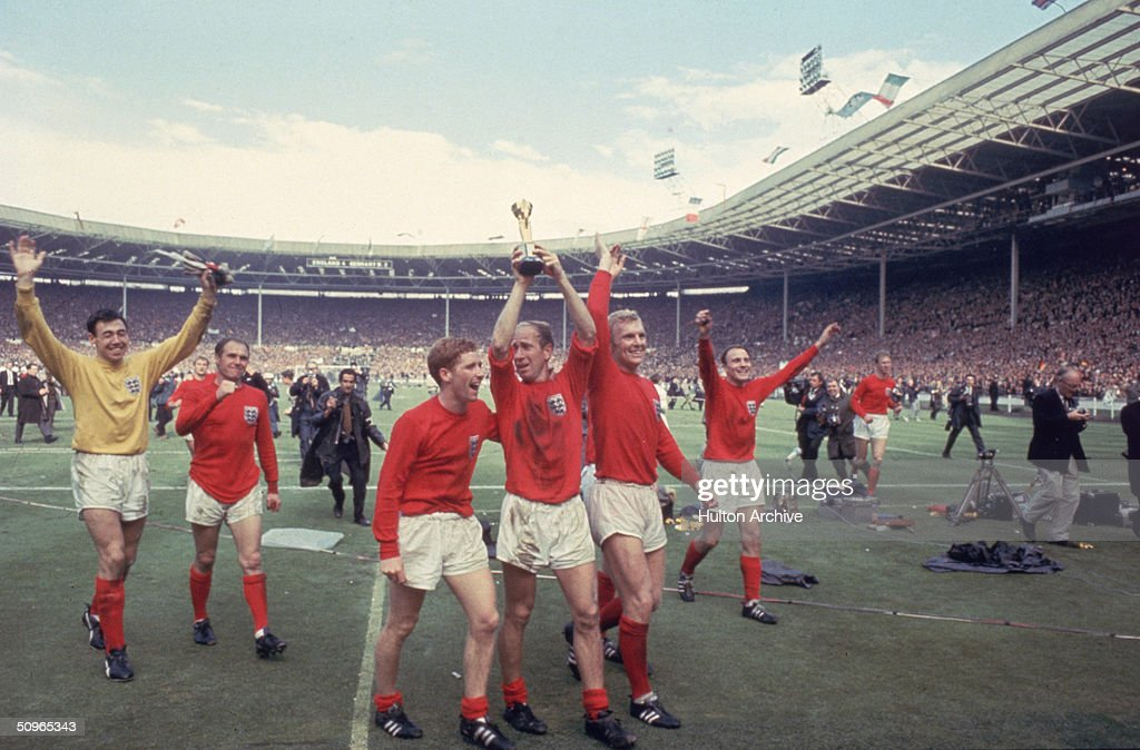 Bobby Charlton raises the Jules Rimet trophy in the air following England's 4-2 victory after extra time over West Germany in the World Cup Final at Wembley Stadium, 30th July 1966. Amongst his team mates celebrating with him are goalkeeper Gordon Banks, Alan Ball on his right and team captain Bobby Moore (1941 - 1993) at his left.