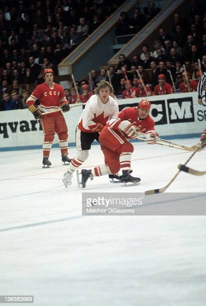 Bobby Clarke of Canada looks to finish the check on Yevgeny Mishakov of the Soviet Union after Mishakov passed the puck during the 1972 Summit Series...