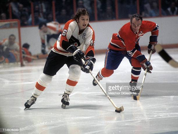 Bobby Clarke of the Philadelphia Flyers skates with the puck as Henri Richard of the Montreal Canadiens follows behind during their game circa 1973...