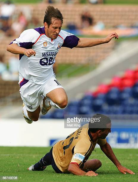 Bobby Despotovski of the Glory jumps over Allan Pickin of the Jets during the round 21 ALeague match between the Newcastle Jets and Perth Glory at...