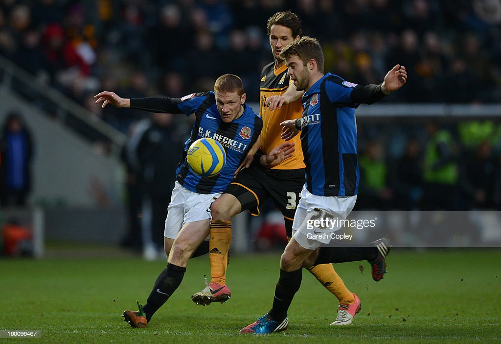 Bobby Hassell and Martin Cranie of Barnsley hold back David Meyler of Hull City during the FA Cup Fourth Round between Hull City and Barnsley at KC Stadium on January 26, 2013 in Hull, England.