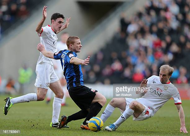 Bobby Hassell of Barnsley is tackled by Luke Chadwick of MK Dons during the FA Cup Fifth Round match between MK Dons and Barnsley at StadiumMK on...