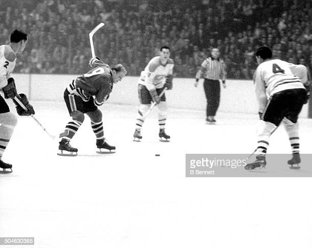 Bobby Hull of the Chicago Blackhawks shoots as Jean Beliveau and Jacques Laperrier of the Montreal Canadiens defend circa 1960's at the Chicago...