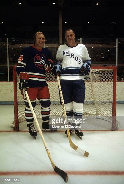 Bobby Hull of the Winnipeg Jets and Gordie Howe of the Houston Aeros lean against the net while posing for the camera during a photo shoot between...