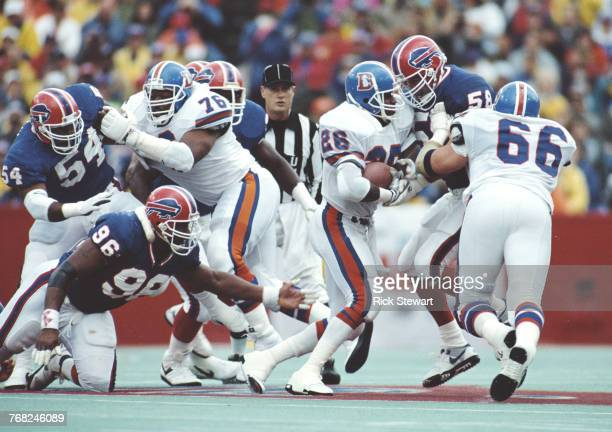 Bobby Humphrey Running Back for the Denver Broncos runs the ball on a play as Shane Conlan Line backer for the Buffalo Bills attempts to block him...