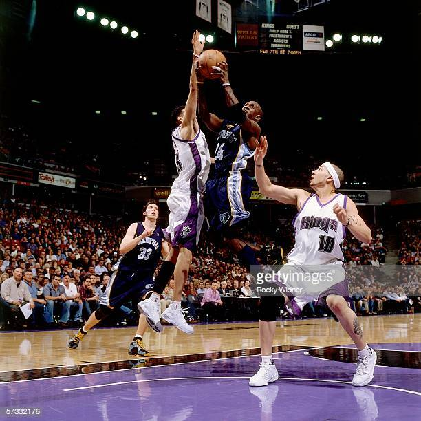 Bobby Jackson of the Memphis Grizzlies takes the ball to the basket against Kevin Martin and Mike Bibby of the Sacramento Kings during the game at...