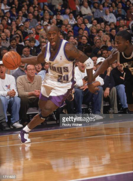 Bobby Jackson of the Sacramento Kings drives around Anthony Goldwire of the San Antonio Spurs during the game at Arco Arena on December 19, 2002 in...