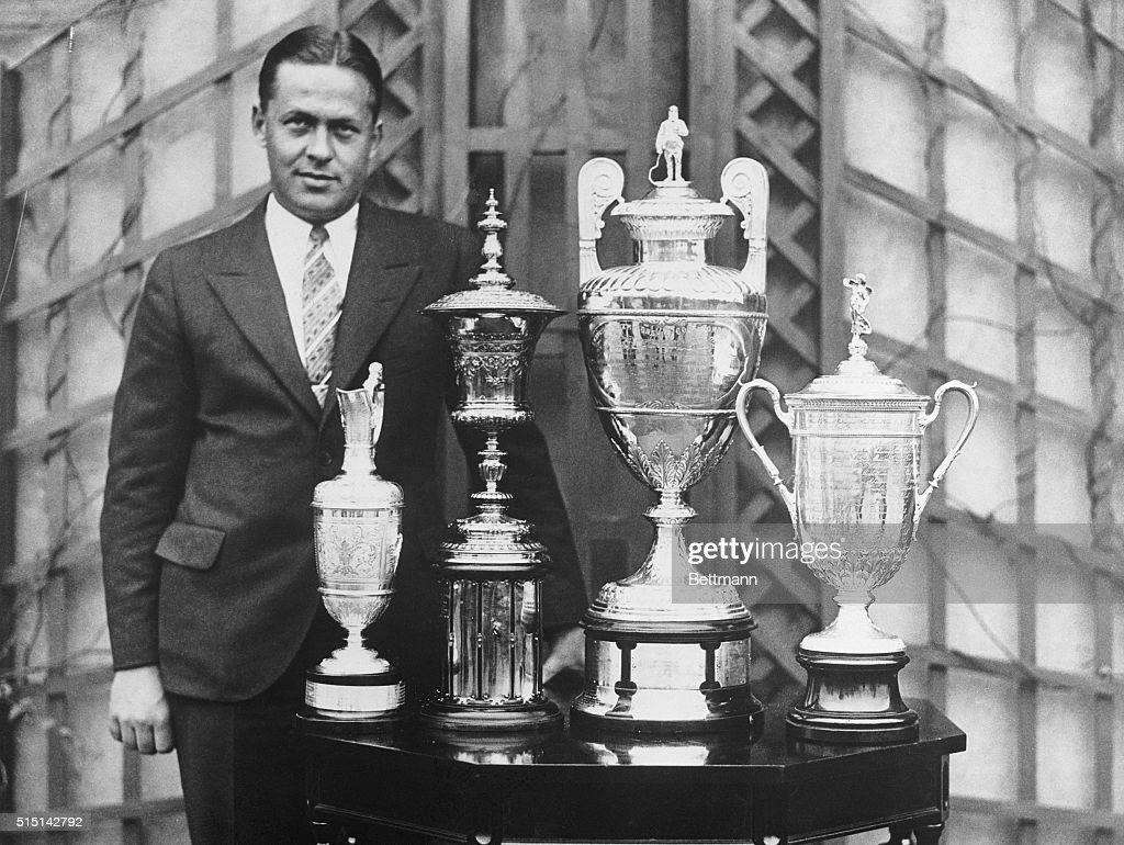 Bobby Jones, American golfer, standing beside the trophies he won for the 'Grand Slam of Golf:' the U.S. Open, the British Open, the U.S. Amateur, and the British Ambassador.
