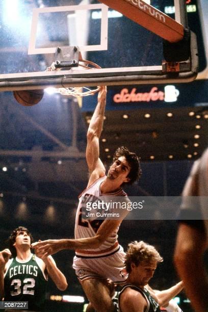 Bobby Jones of the Philadelphia 76ers dunks against Larry Bird of the Boston Celtics in a 1981 season game at the Spectrum in Philadelphia,...