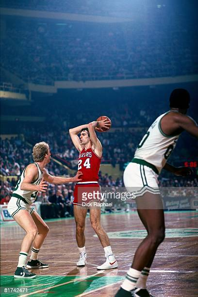 Bobby Jones of the Philadelphia 76ers looks to pass against Larry Bird of the Boston Celtics during a game played in 1983 at the Boston Garden in...