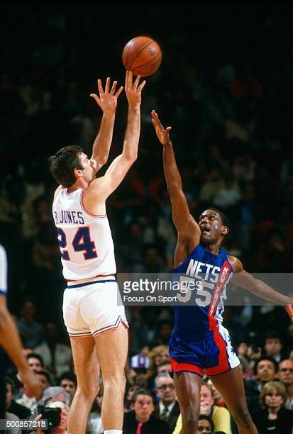 Bobby Jones of the Philadelphia 76ers shoots over Albert King of the New Jersey Nets during an NBA basketball game circa 1984 at The Spectrum in...