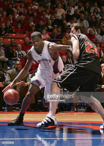 Bobby Jones of the Washington Huskies drives with the ball against Matt Kemper of the Pacific Tigers during the 2005 NCAA division 1 men's basketball...