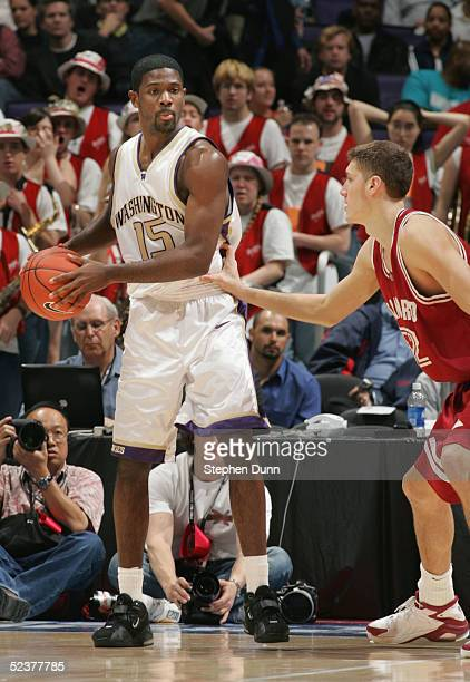 Bobby Jones of the Washington Huskies looks to pass under pressure from Matt Haryasz of the Stanford Cardinal during the 2005 Pacific Life Pac-10...
