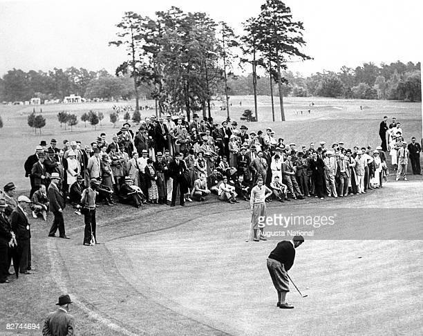 Bobby Jones putts on the 8th green while Horton Smith watches in front of a gallery of patrons during the 1934 Masters Tournament at Augusta National...