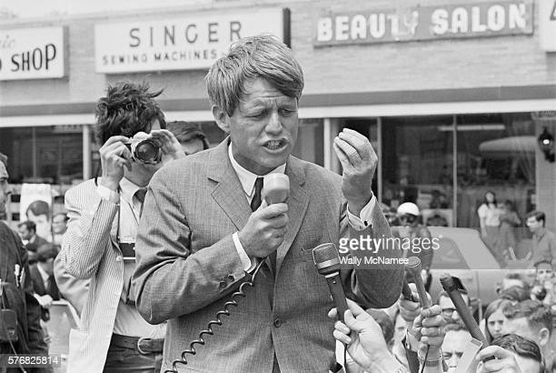 Bobby Kennedy speaks to supporters as he campaigns standing up in an open convertible in Lafayette Indiana during the 1968 Indiana Presidential...